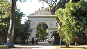 people on bycicles by an arch in Villa Borghese Rome